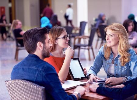 educação: grupo de alunos que trabalha no projeto da escola em conjunto no computador tablet na universidade moderna