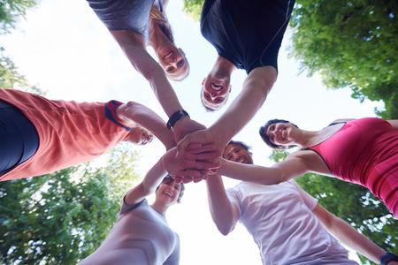 사람들이 그룹 조깅, 친구, 재미, 포옹을 가지고 훈련 후 함께 손을 스택