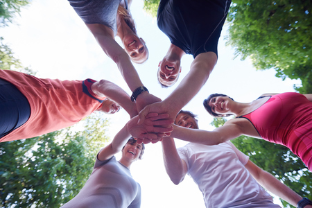Trotar grupo de gente, los amigos se divierten, abrazo y se apilan las manos después del entrenamiento Foto de archivo - 46423094