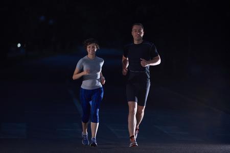 personas corriendo: deportes urbanos, trotar pareja sana en la ciudad en la madrugada en la noche Foto de archivo