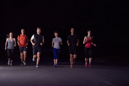 nighttime: people group jogging at night, runners team on early morning  training Stock Photo