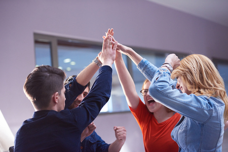 cheerful: happy students celebrate, friends group together at school,  young people raise hands, stack and get in circle  formation together