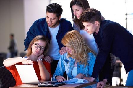 mujeres juntas: grupo de estudiantes trabajando en proyecto de la escuela juntos en la computadora de la tableta en la universidad moderna