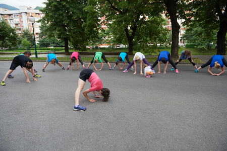 healthy exercise: jogging people group stretching in park before training