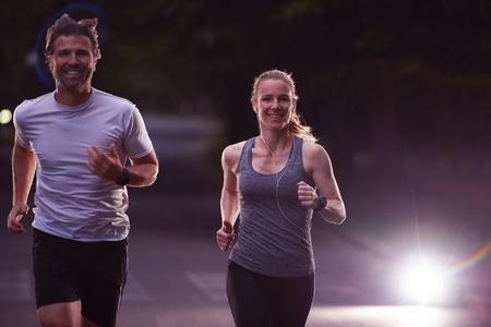 fitness hombres: deportes urbanos, trotar pareja sana en la ciudad en la madrugada en la noche Foto de archivo