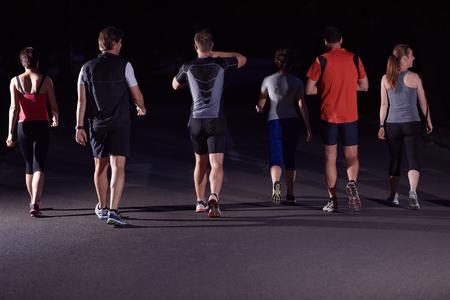 hacer footing: grupo de personas a correr por la noche, los corredores del equipo en el entrenamiento de la mañana