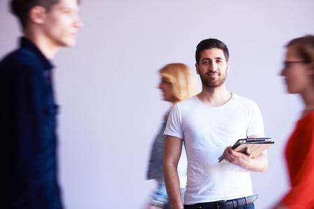 trabajando en casa: estudiante que trabaja en la computadora de la tableta en la escuela universitaria interior moderno, grupo de gente que pasa en el fondo y hacer rutas de movimiento