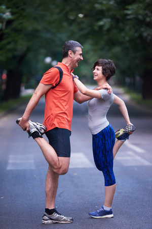 mature women: jogging couple warming up and stretching before running