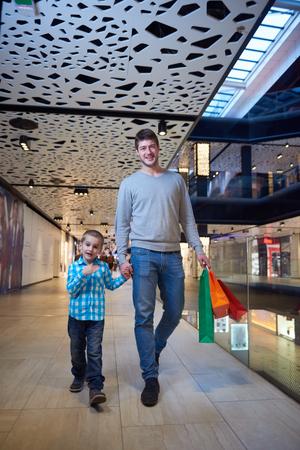 centro comercial: familia joven feliz con bolsas de compras en centro comercial Foto de archivo