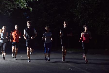 groupe de personnes du jogging à la nuit, les coureurs équipe sur la formation du matin