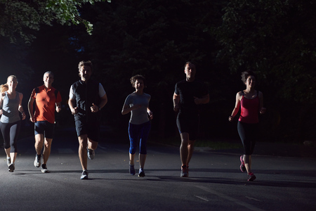 people group jogging at night, runners team on early morning  training Stock Photo