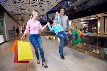 happy shopping: happy  young family with shopping bags in mall