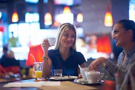 belle brune: heureux amies ont tasse de café dans un restaurant de la ville moderne