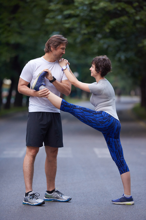 sport woman: jogging couple warming up and stretching before running