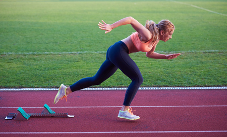 jogging: pixelated design of woman  sprinter leaving starting blocks on the athletic  track. Side view. exploding start Stock Photo
