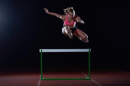 Déterminé jeune femme athlète sautant par-dessus un haies Banque d'images