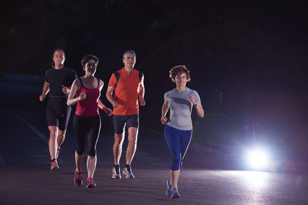 morning night: people group jogging at night, runners team on early morning  training Stock Photo
