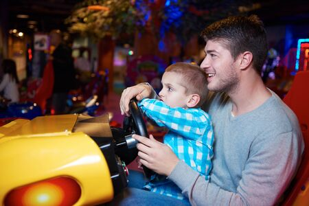 family in park: happy father and son playing driving wheel video game in playground theme park Stock Photo