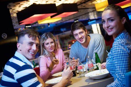 socializando: amigos tienen descanso lancha en el centro comercial, comer comida rápida italiana Foto de archivo