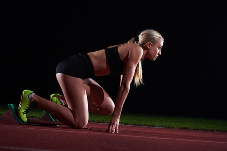 athletes: pixelated design of woman  sprinter leaving starting blocks on the athletic  track. Side view. exploding start Stock Photo