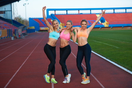 outdoor exercise: athlete woman group  running on athletics race track on soccer stadium and representing competition and leadership concept in sport