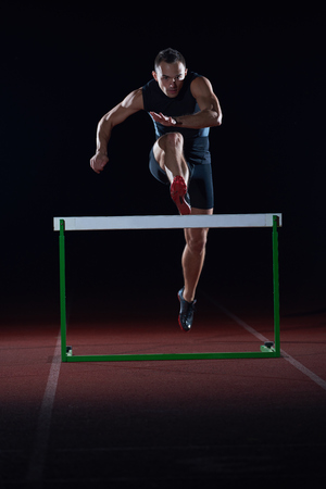 athletics: man athlete jumping over a hurdles on athletics race track Stock Photo
