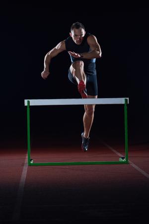 man athlete jumping over a hurdles on athletics race track Standard-Bild