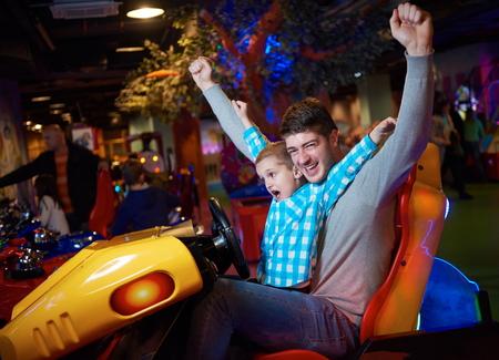feliz padre e hijo jugando conducción rueda de videojuegos en el parque temático parque infantil