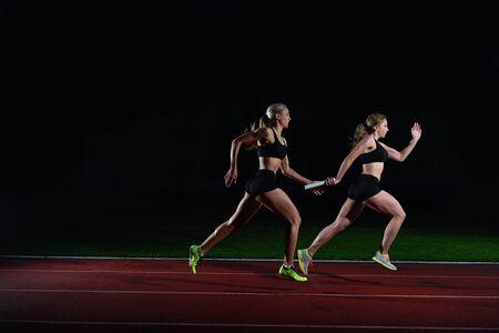 relay: mujer corredores de atletismo que pasan el bastón en carrera de relevos Foto de archivo