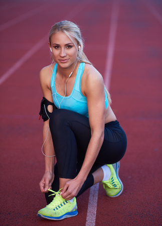 woman muscle: young runner sporty woman relaxing and stretching on athletic race track Stock Photo