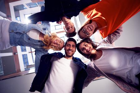 jovenes felices: estudiantes felices celebran, grupo de amigos juntos en la escuela, los jóvenes levantan las manos, se apilan y obtener en la formación de círculo juntos Foto de archivo