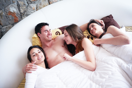 adult sex: young macho playboy handsome man in bed with three beautiful sexy woman