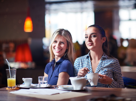 chatting: happy girl friends have cup of coffee in modern city restaurant Stock Photo