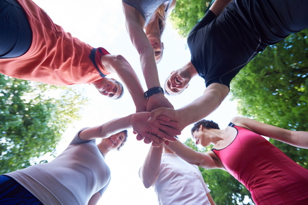 ready: jogging people group, friends have fun,  hug and stack hands together after training