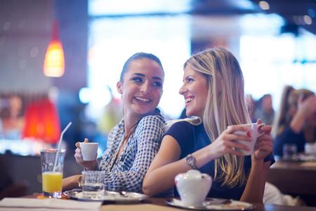 amigos: felices amigas tienen taza de café en el restaurante de la ciudad moderna Foto de archivo