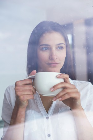 and the rain: beautiful young woman drink first morning coffee at modern home interior with rain drops on big window door glass Stock Photo