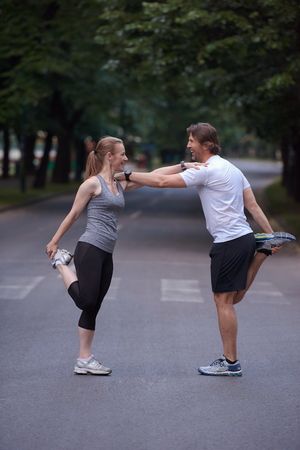 personas saludables: jogging couple warming up and stretching before running