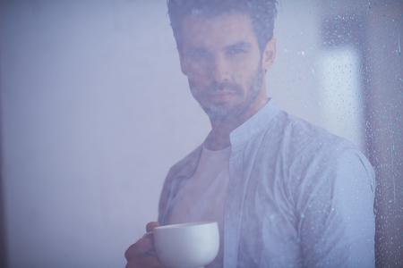 tomando café: joven relajado beber primer café de la mañana en la casa moderna en el interior en la ventana de lluvias cae por la ventana Foto de archivo