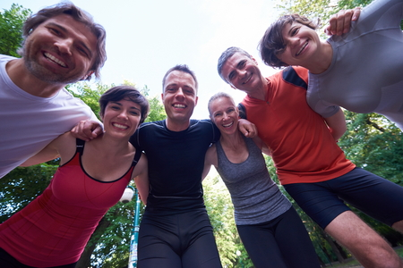 hold hands: jogging people group, friends have fun,  hug and stack hands together after training