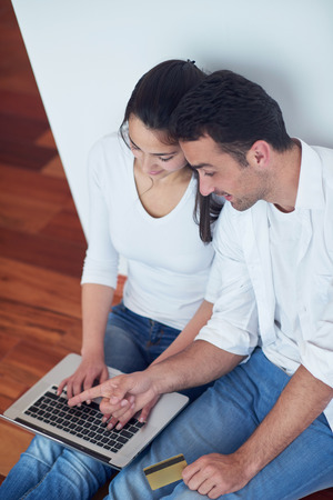 house shopping: happy young relaxed  couple working on laptop computer at modern home interior