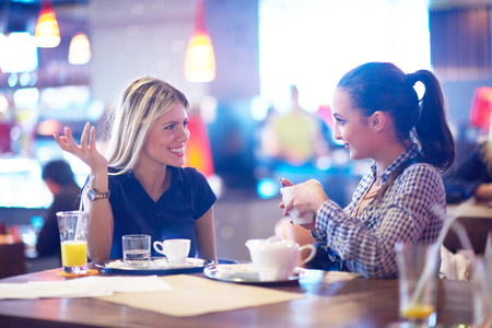 happy girl friends have cup of coffee in modern city restaurant Archivio Fotografico