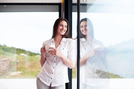 beautiful young woman drink first morning coffee at modern home interior with rain drops on big window door glass Banque d'images