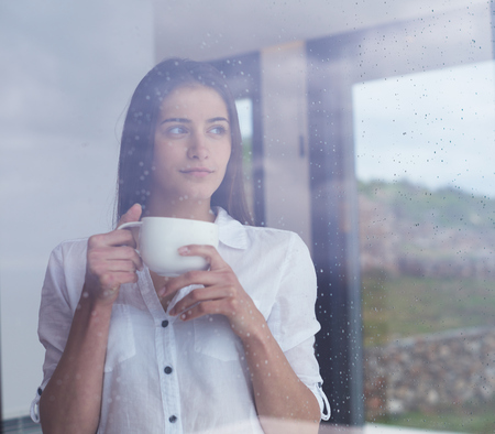beautiful young woman drink first morning coffee at modern home interior with rain drops on big window door glass Stock Photo