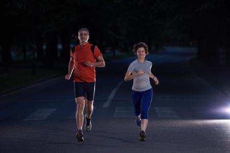 hombres corriendo: deportes urbanos, trotar pareja sana en la ciudad en la madrugada en la noche Foto de archivo
