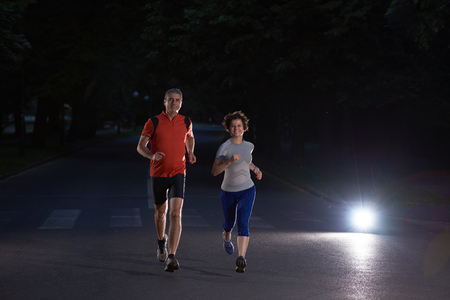 morning night: urban sports, healthy couple jogging in the city at early morning in night Stock Photo