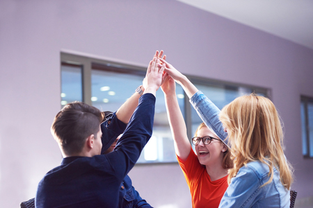 fun at work: happy students celebrate, friends group together at school,  young people raise hands, stack and get in circle  formation together