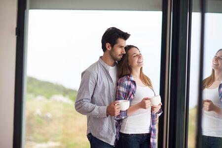 pareja en casa: relaxet joven pareja beber primer café de la mañana sobre gran ventana brillante en moder interior villa casa