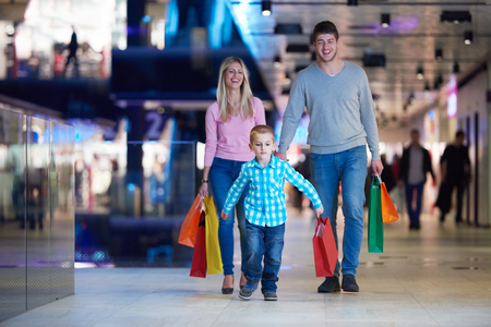retail shopping: happy  young family with shopping bags in mall