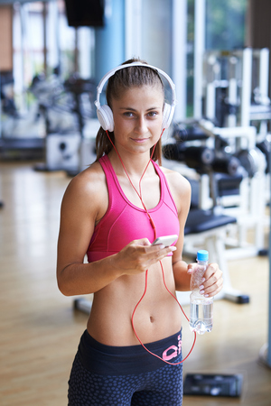 fitness gym: young healthy woman drinking water  in fitness gym while sitting on pilates ball and listening music on headphones from smartphone Stock Photo
