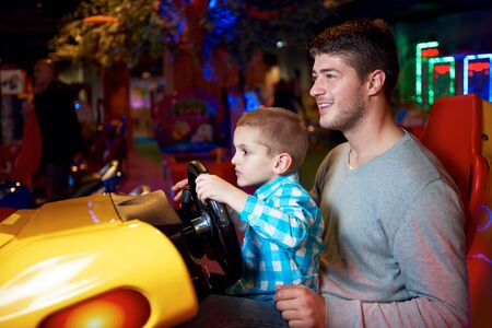 playground ride: happy father and son playing driving wheel video game in playground theme park Stock Photo